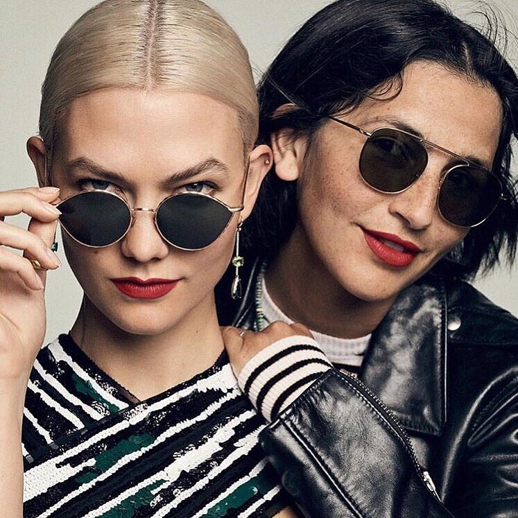 Two women posing with Optiko sunglasses in modern outfits