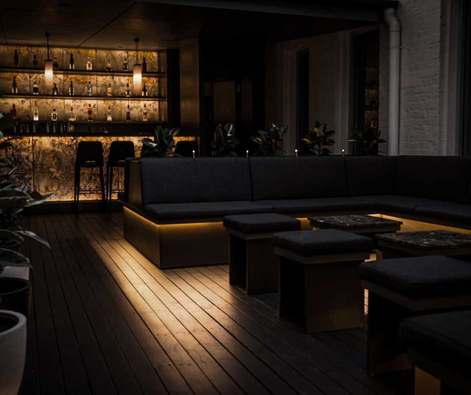 Interior of Cloakroom brisbane, black couches and soft backlighting
